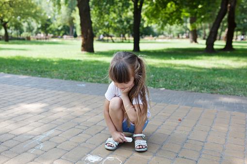 1019302738 istock photo Child cute girl draws with chalk on the asphalt. Asphalt street art. Kids education. Childhood 1169360408