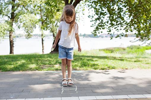 1019302738 istock photo Child cute girl draws with chalk on the asphalt. Asphalt street art. Kids education. Childhood 1169377068