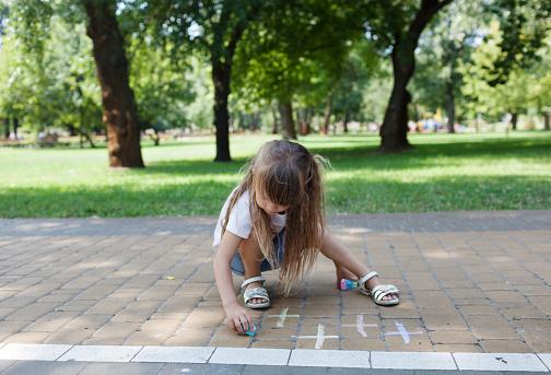 1019302738 istock photo Child cute girl draws with chalk on the asphalt. Asphalt street art. Kids education. Childhood 1169377076