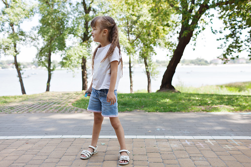 1019302738 istock photo Child cute girl draws with chalk on the asphalt. Asphalt street art. Kids education. Childhood 1169379635
