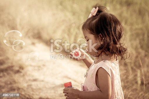 507271044istockphoto Child cute little girl blowing a soap bubbles 496703118