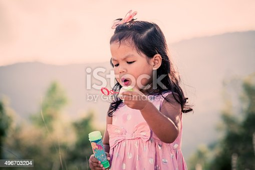 507271044istockphoto Child cute little girl blowing a soap bubbles 496703204