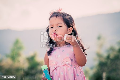 507271044istockphoto Child cute little girl blowing a soap bubbles 496703302