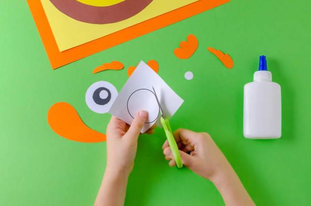 kind schneidet papier kreis, ansicht von oben, klebstoff und schere auf grün - diy eule stock-fotos und bilder
