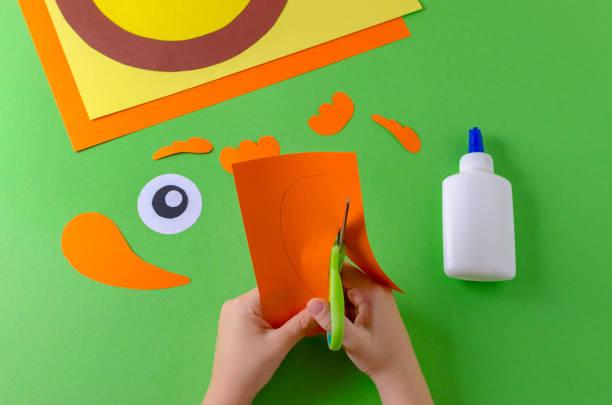 kind schneidet papier abbildung, ansicht von oben, klebstoff und schere auf grün - diy eule stock-fotos und bilder