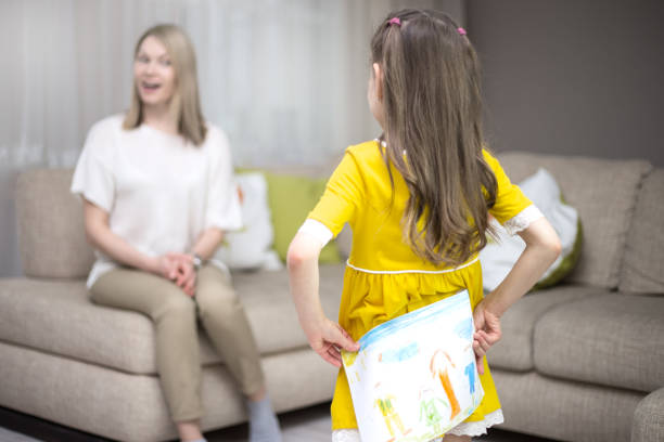child daughter congratulates mom and gives her painting. mum and girl smiling and hugging. - little girls giving head stock photos and pictures