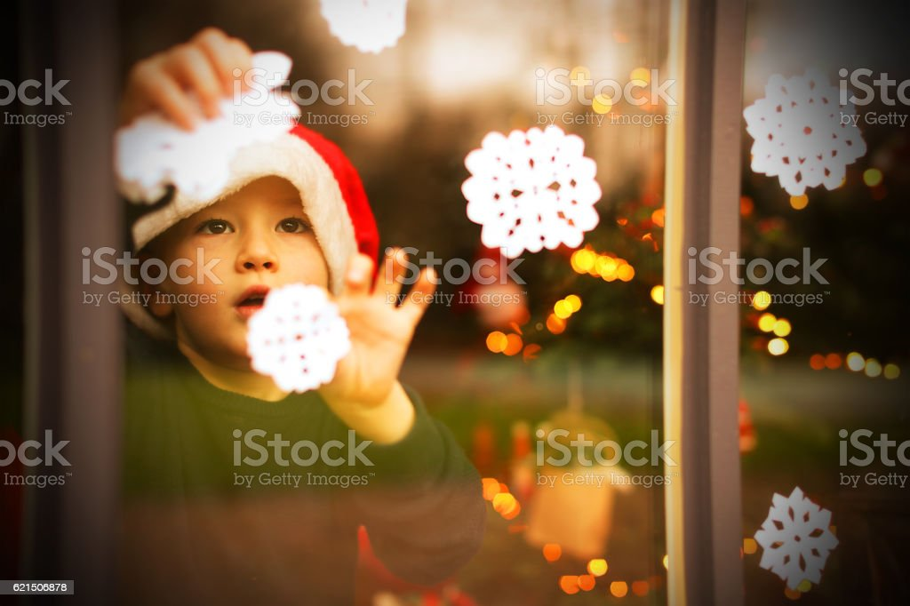 Child Decorating a Window with Snowflakes for Christmas photo libre de droits