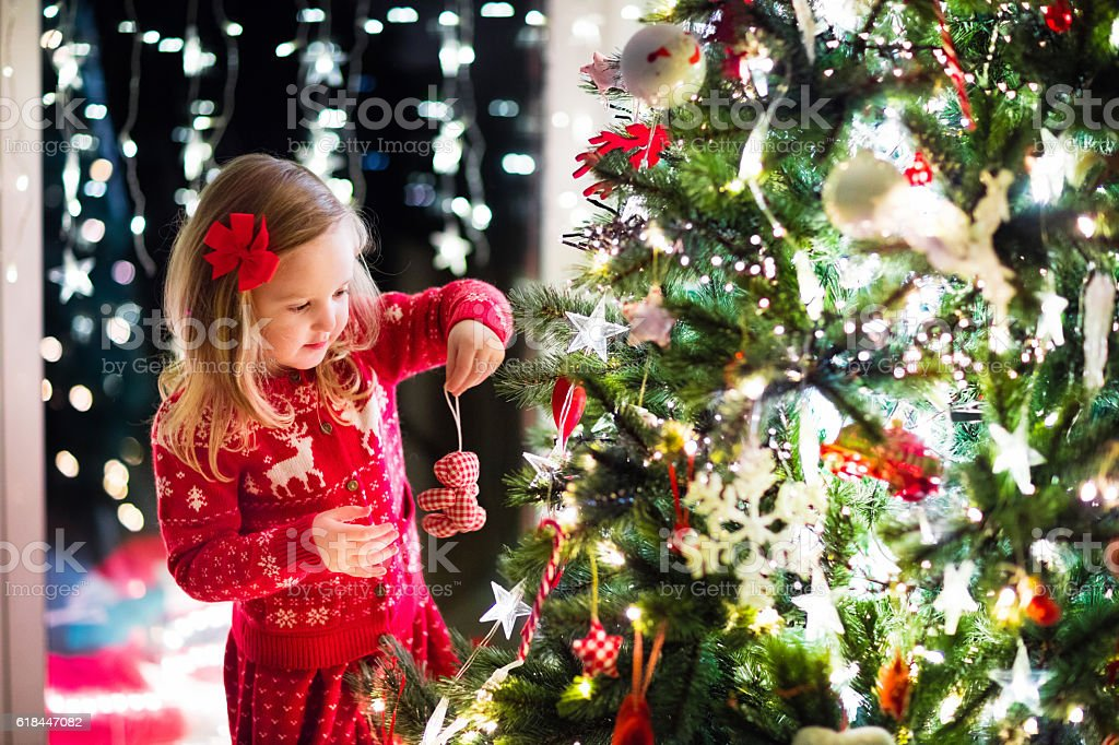Child decorating Christmas tree in family living room with fireplace stock photo