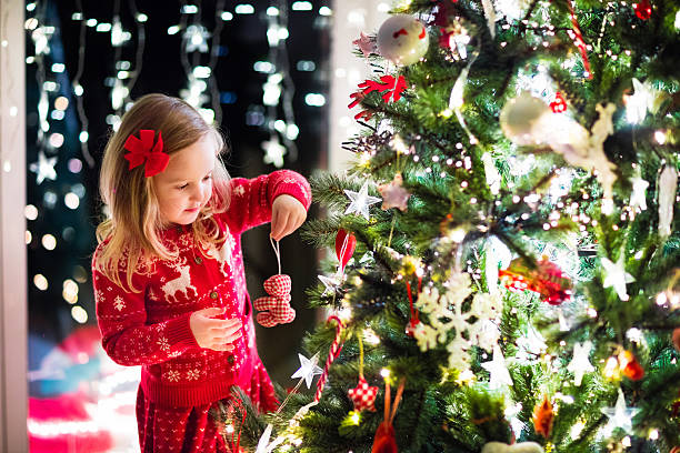 Child decorating Christmas tree in family living room with fireplace - foto stock