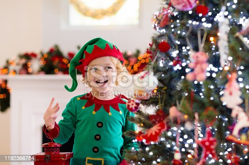 cute little boy in gray pajamas and a Santa Claus hat rests on the floor under the Christmas tree among the holiday gift boxes