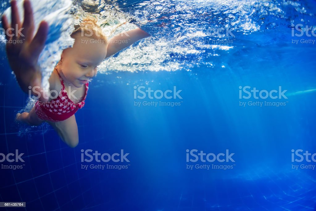 Child diving underwater in swimming pool stock photo