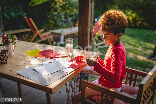 Lovely mixed race child doing art project homework.