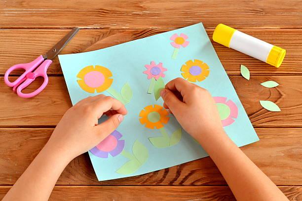 child doing a card with flowers - origami anleitungen stock-fotos und bilder