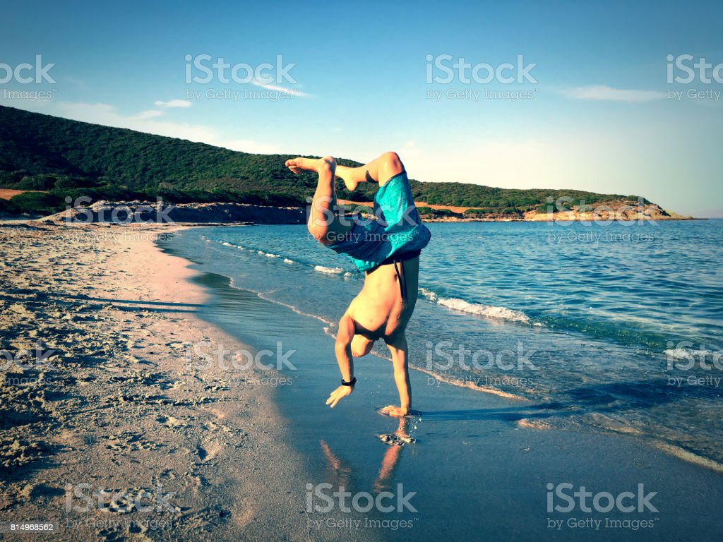 Child doing a handstand on beach stock photo