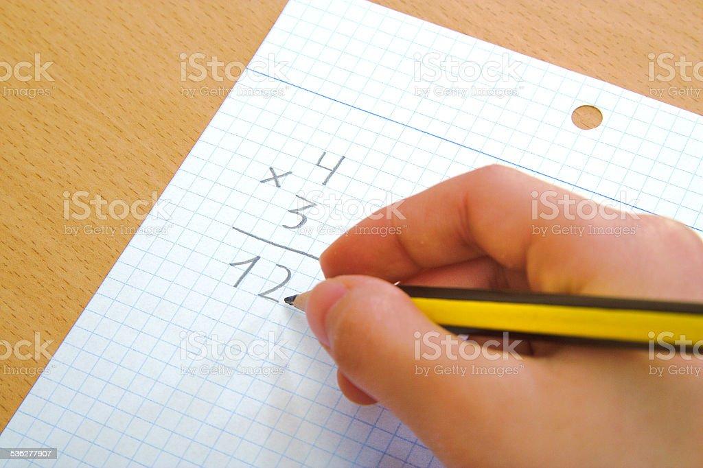 Child doing a math multiplication as homework stock photo