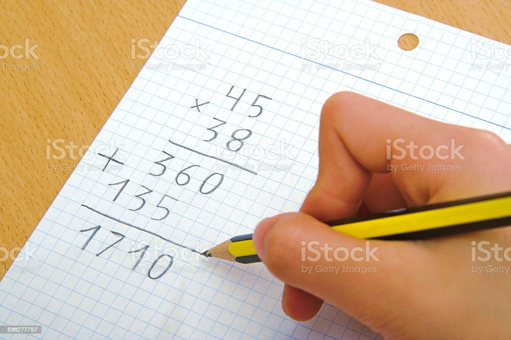 Child doing a math multiplication at school stock photo