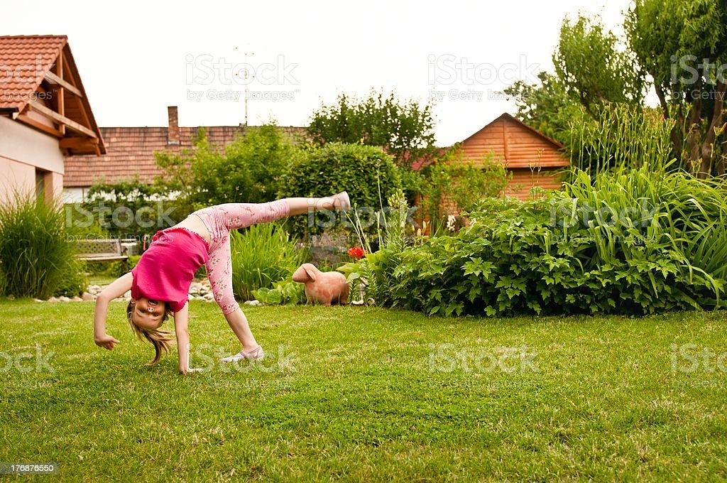 Child doing cartwheel in backyard stock photo