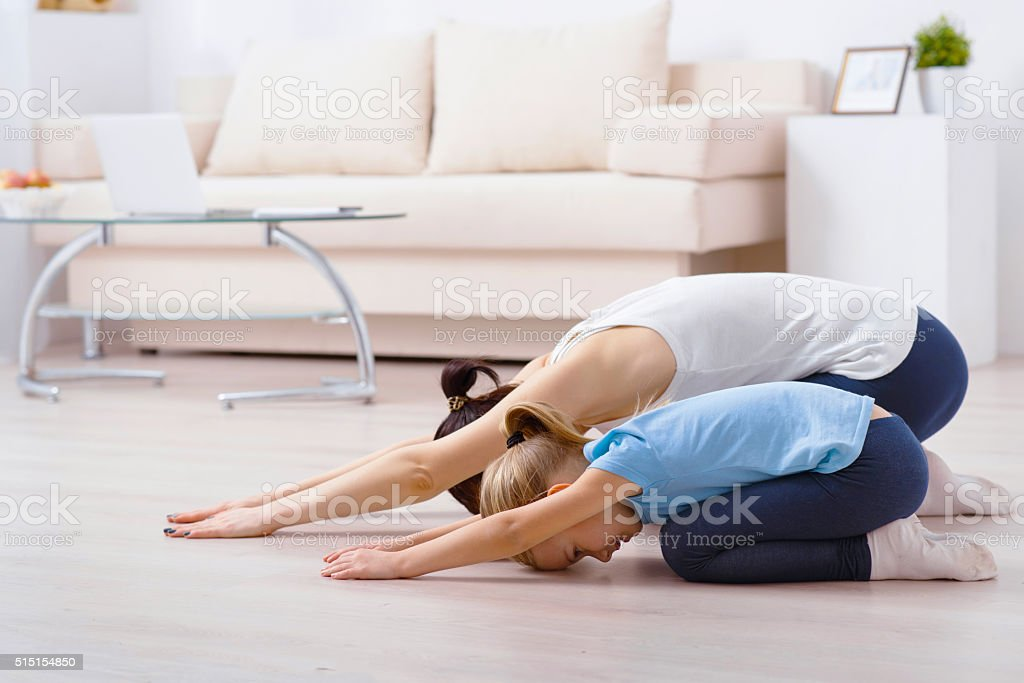 Child doing exercises with mother stock photo