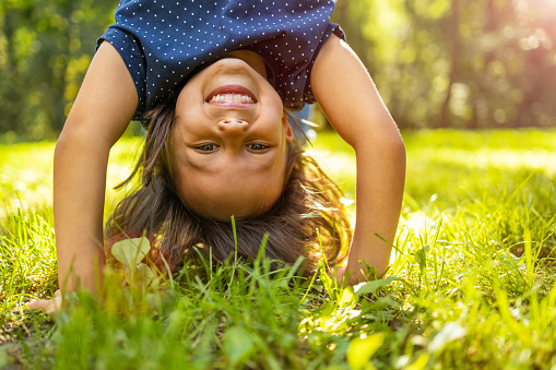 Little girl standing upside down in park