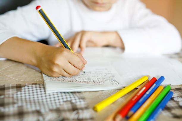 child doing homework and writing story essay. elementary or primary school class. closeup of hands and colorful pencils - {{asset.href}} foto e immagini stock