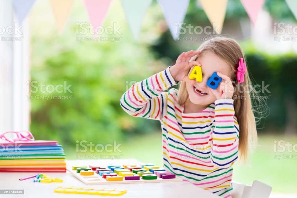 Child doing homework for school. Kids learn and paint. stock photo
