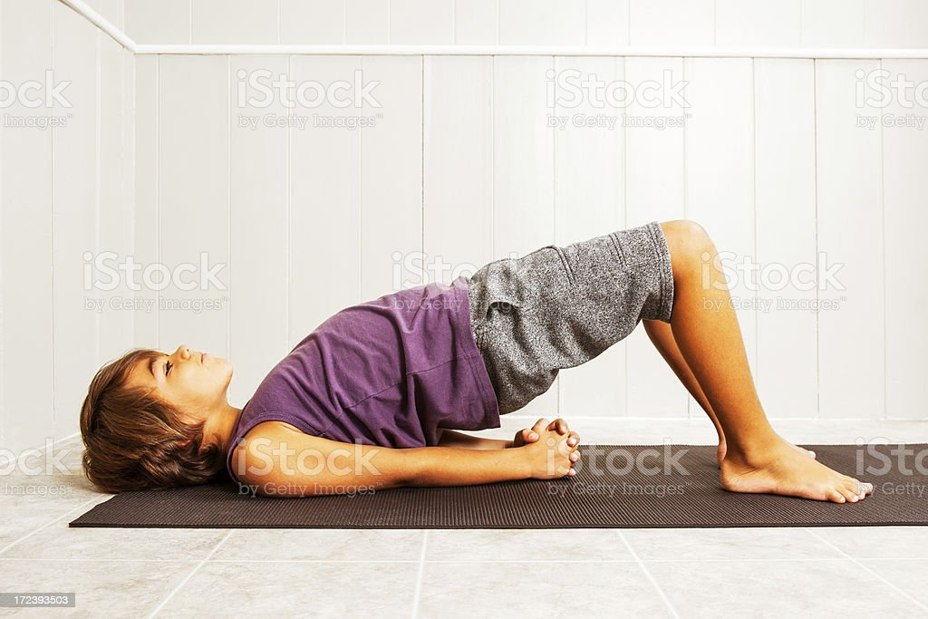 Child doing the bridge yoga pose royalty-free stock photo
