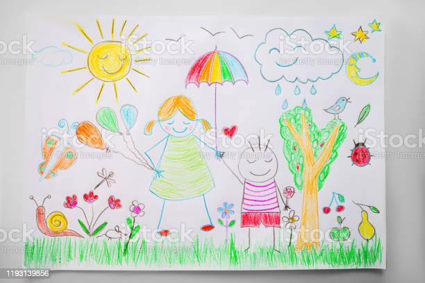Photo of Child drawing a happy family with color pencils
