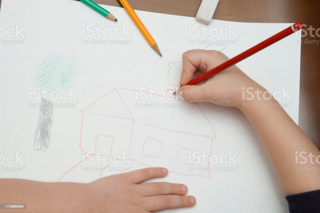 A child drawing a house with colored pencils on white paper stock photo