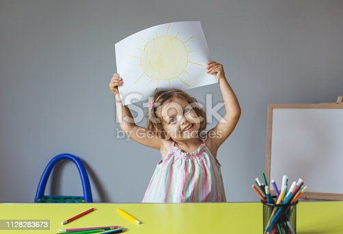 Happy little girl holding drawing of a sun at home