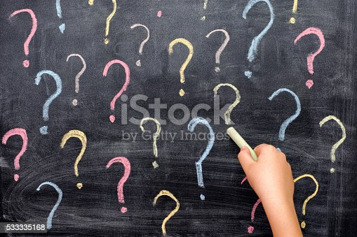 Child drawing colorful question marks on blackboard. Close up.