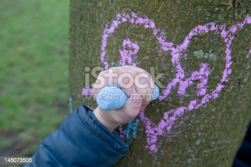 istock Child drawing heart on a tree trunk 145073505