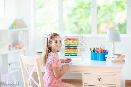istock Child drawing. Kids paint. Girl after school. 1129700895