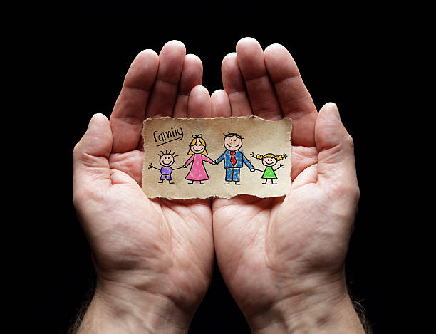 Child drawing of family with the protection of cupped hands - Photo
