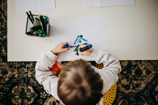 Child drawing on paper in living room