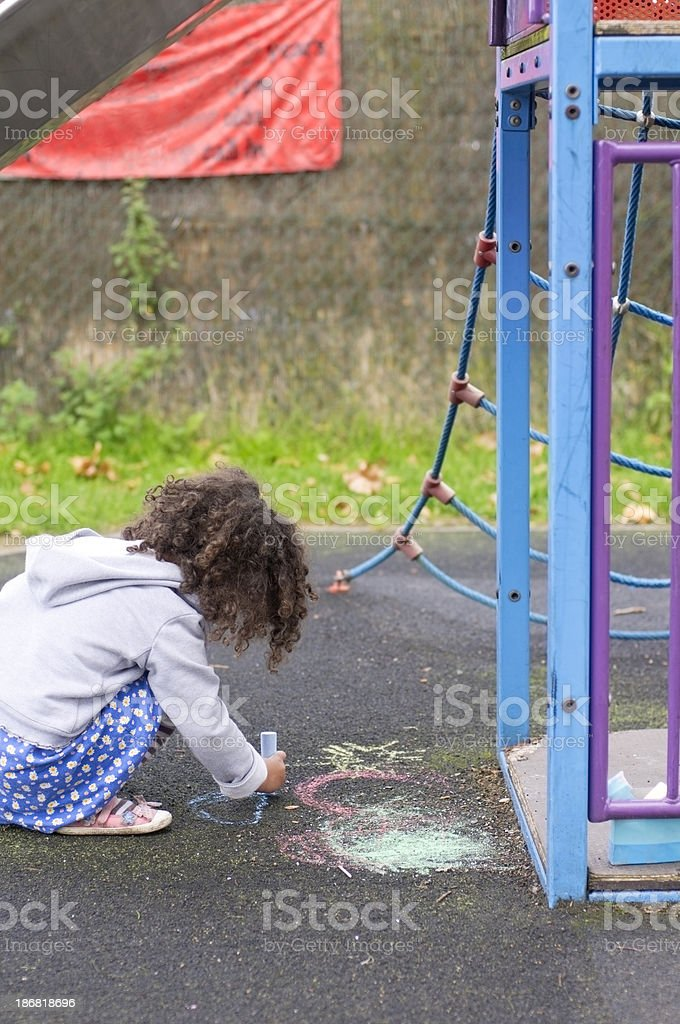 Child (4-5) Drawing on the Ground in Playground stock photo