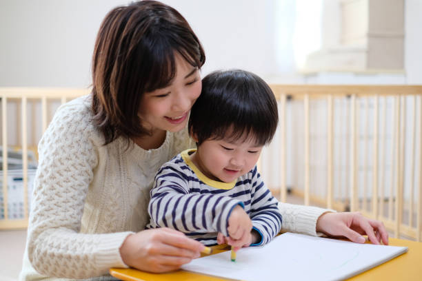 Child drawing picture with mother at home Everyday life of baby with mother and toddler at home homemaker stock pictures, royalty-free photos & images