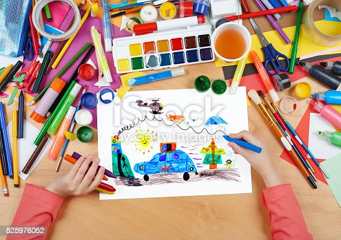 istock child drawing police car and helicopter, top view hands 525976052
