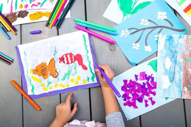 Kind zeichnen. Draufsicht des Kinderhände mit Bleistift Gemälde Bild auf Papier. Kid Zeichnungen. – Foto