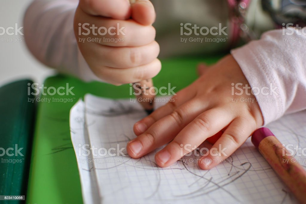 Child drawing with crayons on a piece of paper stock photo