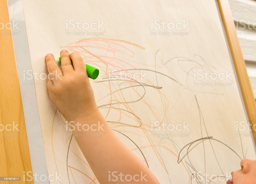 Child drawing with crayons stock photo