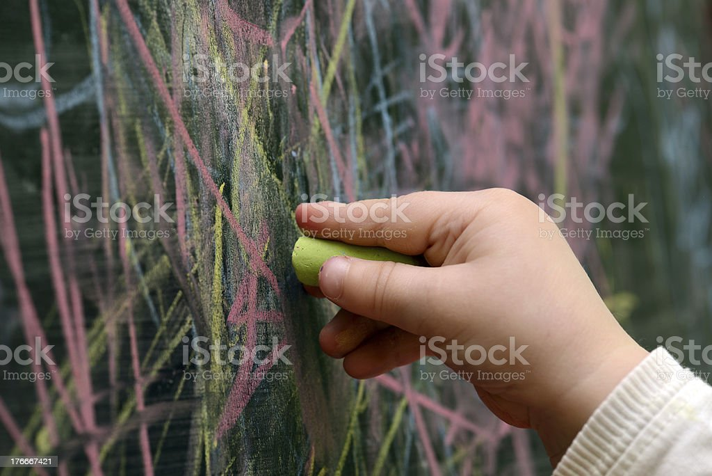 child draws with chalk on a blackboard royalty-free stock photo