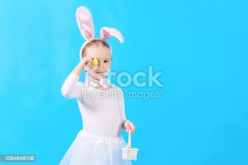 155096501 istock photo A child dressed as a white Easter bunny. The little girl in her hands holds a small basket and an Easter egg. Copy space. Bright photo with place for text. 1094649106