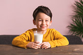Child drinking a glass of milk. He loves milk. He knows that he needs to drink milk for healthy bones.