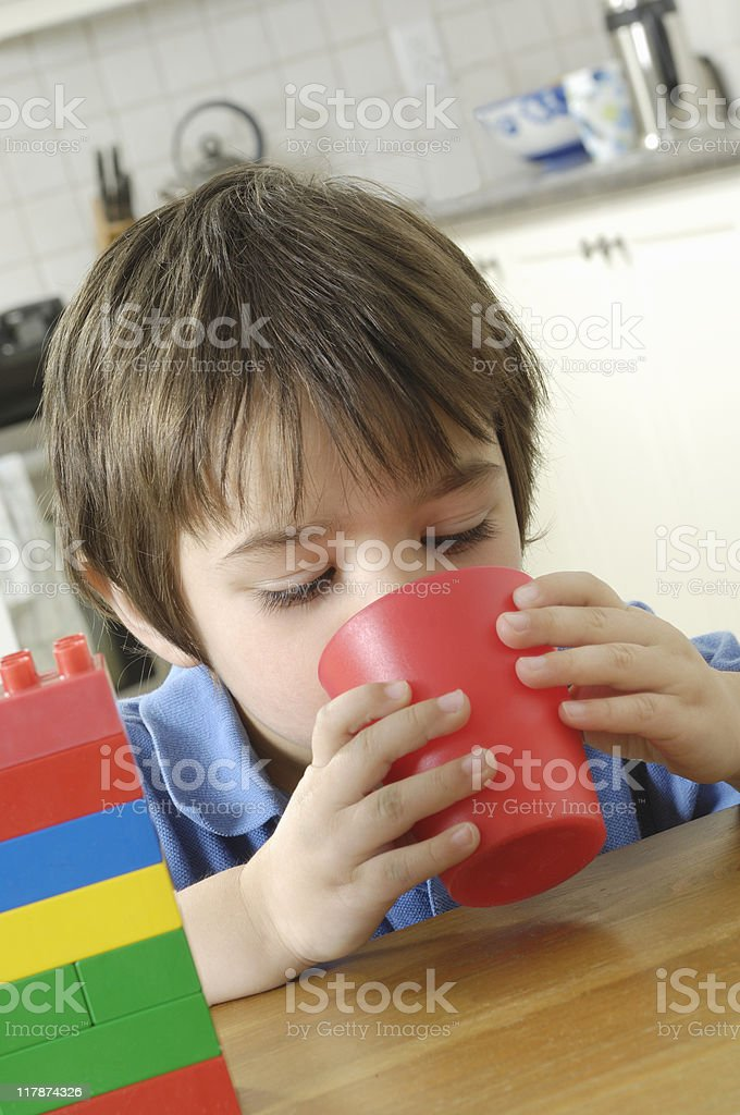 Child drinking at a kitchen table stock photo