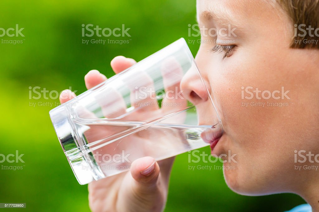 Child drinking glass of fresh water stock photo