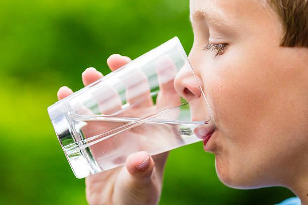 Bambino bere un bicchiere di acqua dolce - foto stock
