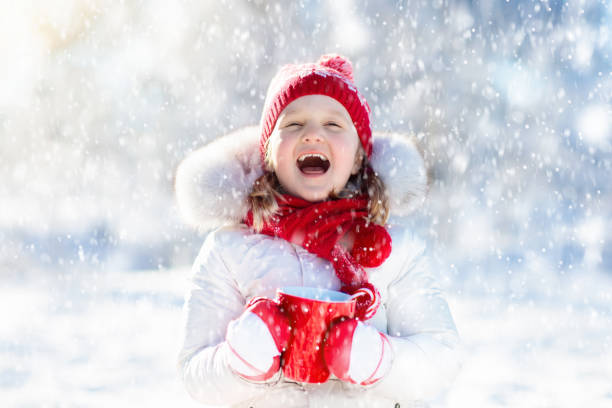 Child drinking hot chocolate in winter park. Kids in snow on Christmas. stock photo
