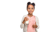 cute african american child drinking milk and showing thumb up isolated on white