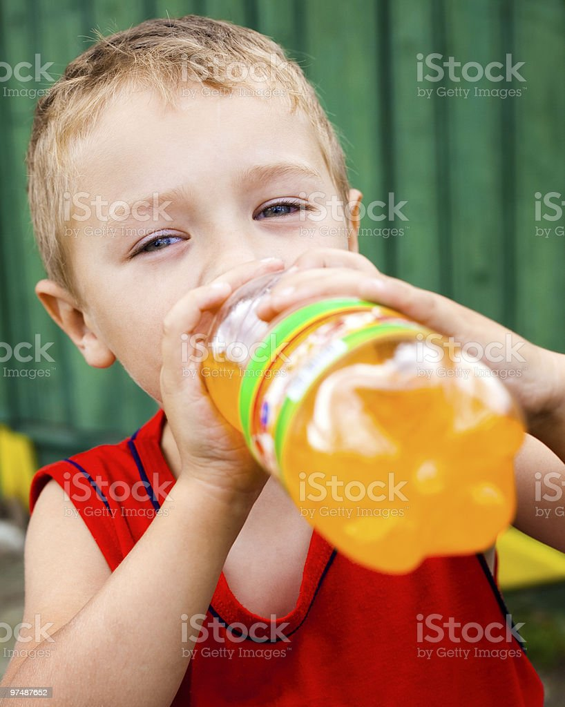 Child drinking unhealthy bottled soda royalty-free stock photo