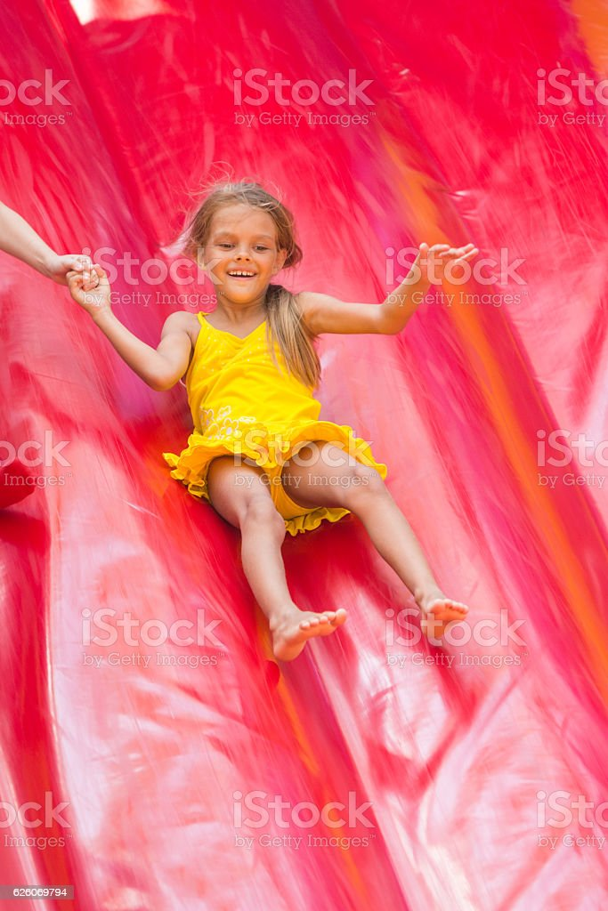 Child drives off the high inflatable trampoline stock photo